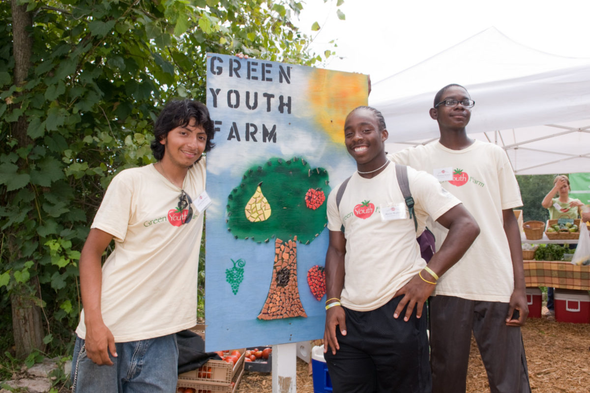 "Teens with ""Green Youth Farm"" sign"