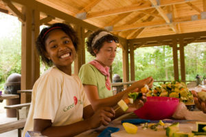 Two teenage girls making fruit kabobs with a big smile