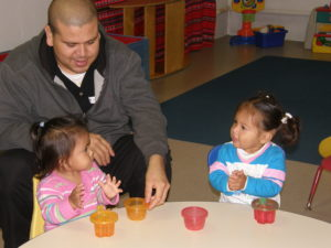 A man playing with his two daughters at the kids table